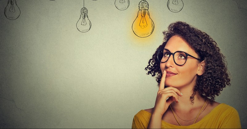 Woman looking up at a lightbulb