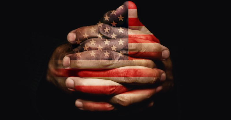 praying hands imprinted with Amerian flag
