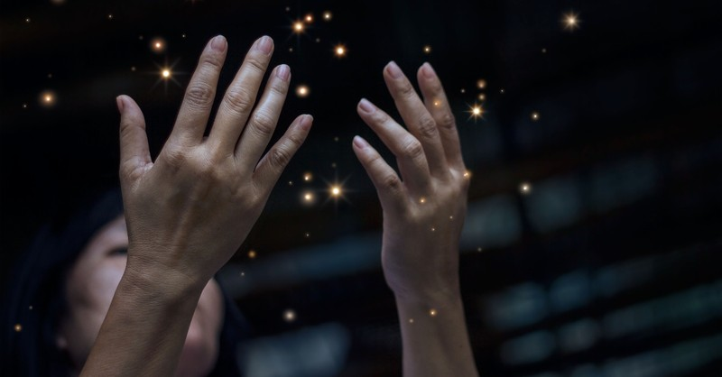 Woman holding her hands up in Disbelief with sparks