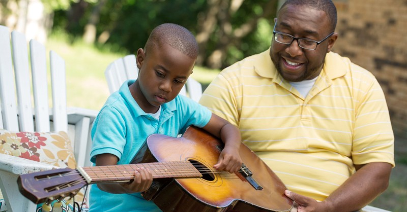 dad teaching son to play guitar