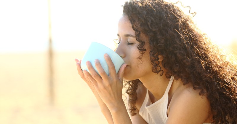 young woman drinking coffee outdoors at peace