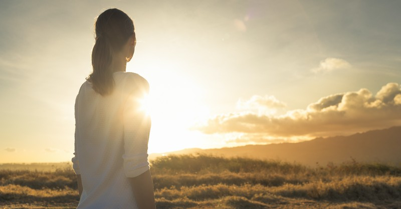 hopeful woman looking out toward sunrise over field