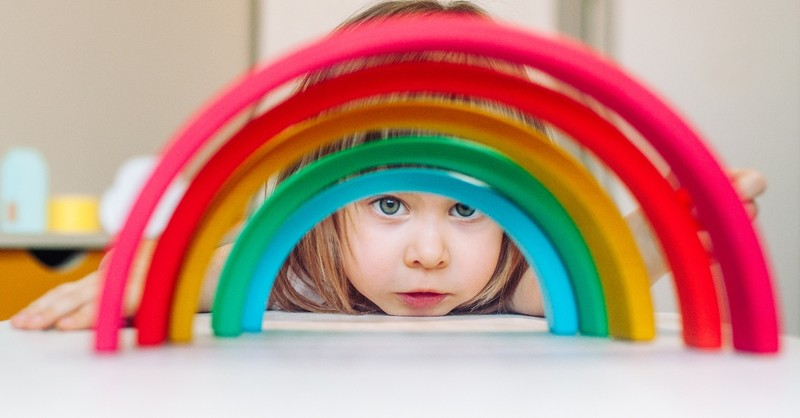 little girl looking through toy rainbow, how should parents talk to their kids about lgbtq issues?