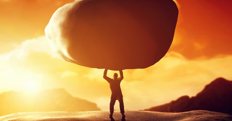 man holding large boulder at sunset bible story of cain and abel