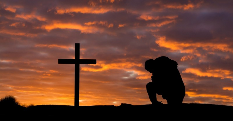 Man kneeling before the cross