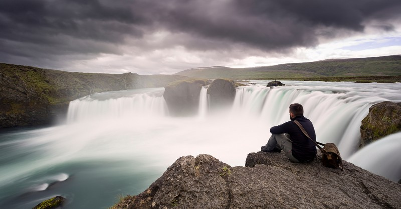 man marveling in awe at edge of waterfall - god-fearing