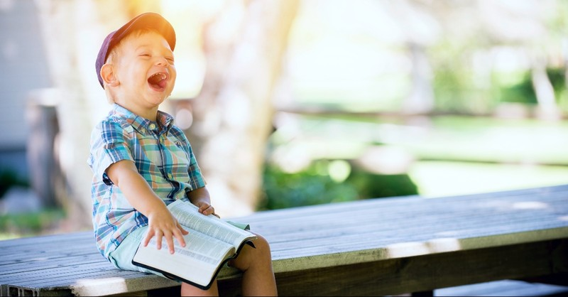 A little boy laughing with a Bible on his lap