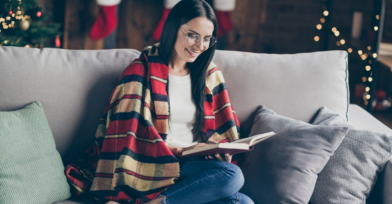 woman with blanket reading by fireplace first Sunday of Advent