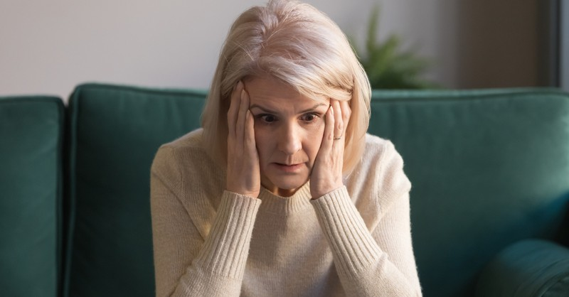 senior mature woman upset and stressed looking at laptop