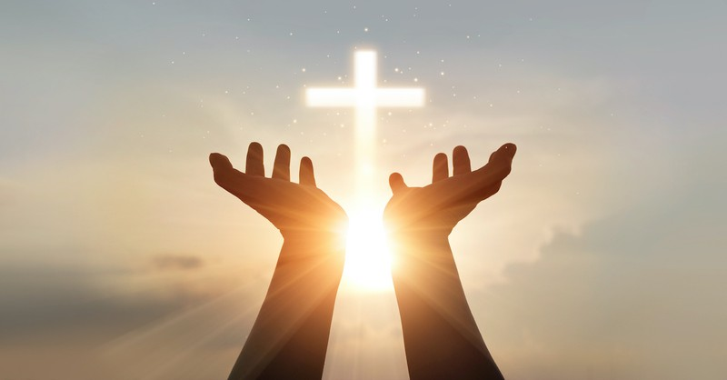 silhouette of raised hands toward cross graphic in bright sky