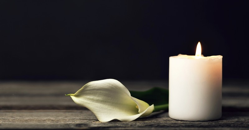 White candle in remembrance and a lily