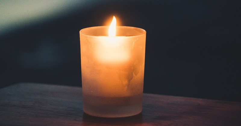 lone candle light in dark setting, hymns for trusting God in grief