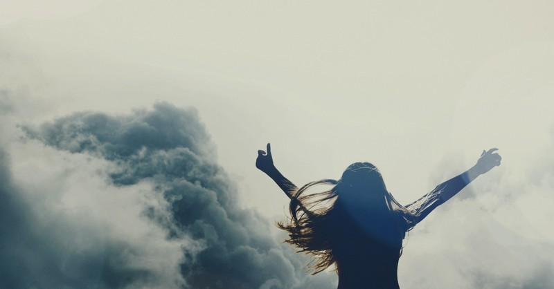 woman with arms raised with clouds behind, where the spirit of the lord is there is freedom
