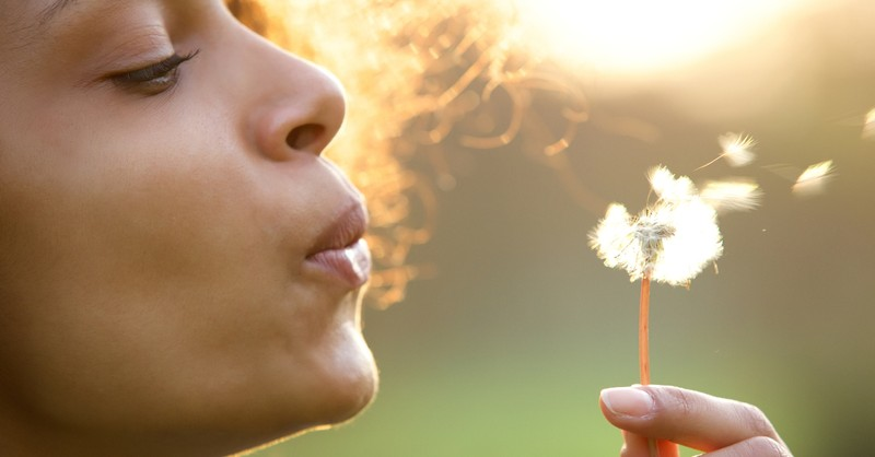 woman blowing dandelion letting go of worry