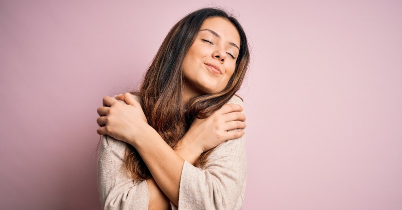woman hugging herself feeling in love, what the world gets wrong about love
