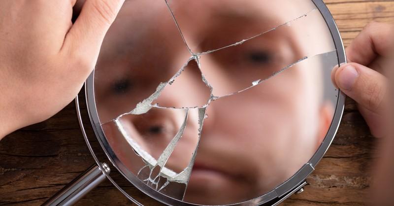 man looking into broken hand mirror pastor reflecting