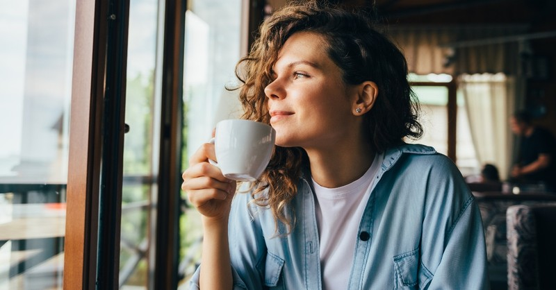 young woman drinking coffee looking outside in cafe restaurant, ways to make your every day more meaningful