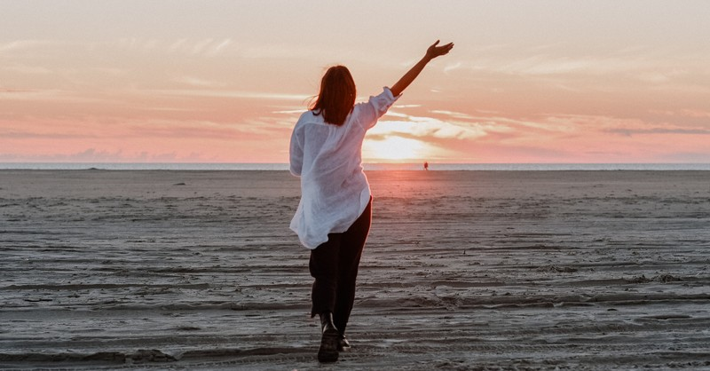 woman walking on empty beach giving praise and thanks in season of loss