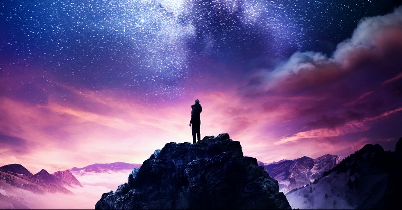 Man on top of a mountain with stars and clouds