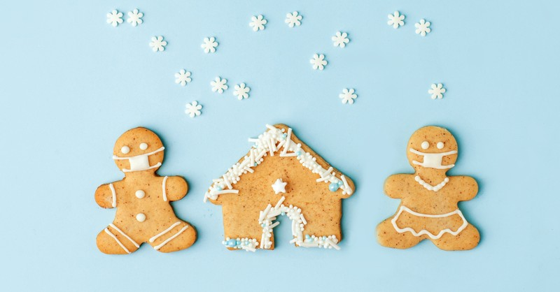 gingerbread couple in christmas snow scene during pandemic wearing face masks