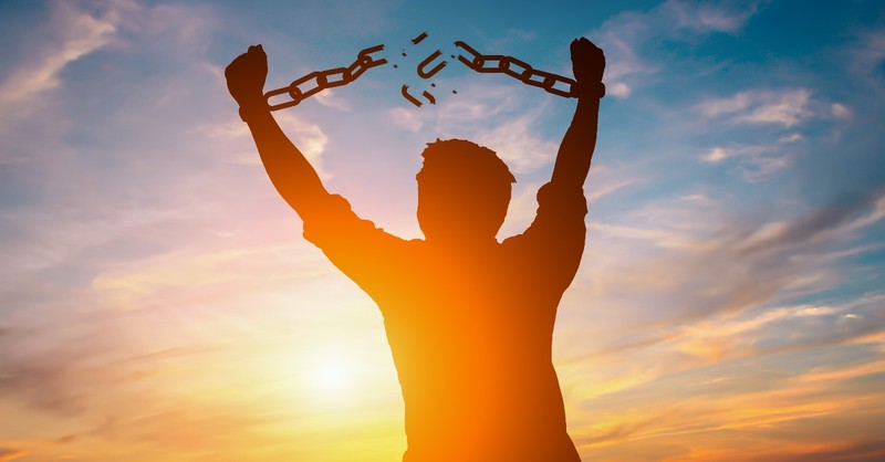 silhouette of man breaking free from chains, how to stop living in your past and seize your future