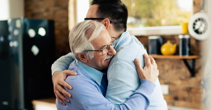 happy senior mature dad hugging prodigal adult son