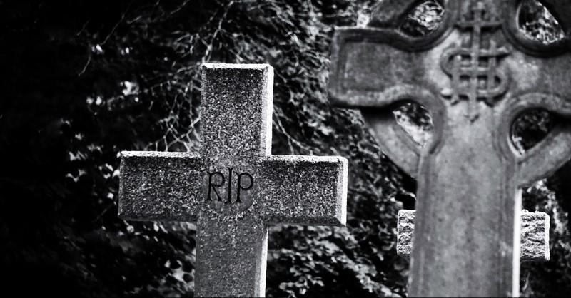Cross headstone that reads RIP