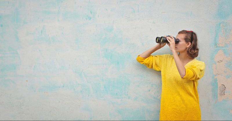 Woman looking around through binoculars
