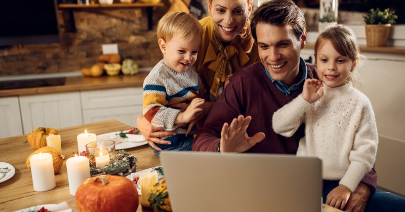 family smiling over zoom thanksgiving