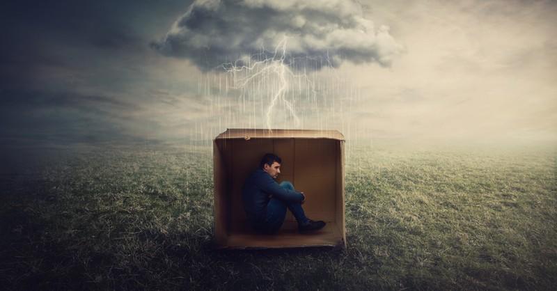scared man hiding in cardboard box in storm unhealthy beliefs