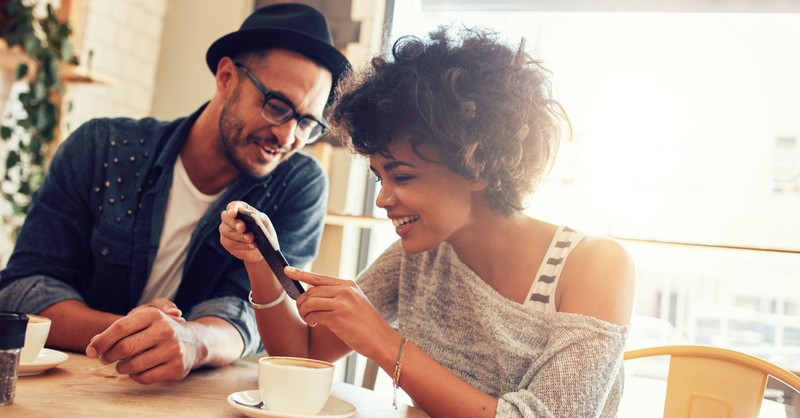 diverse friends laughing at tiktok or video on smartphone