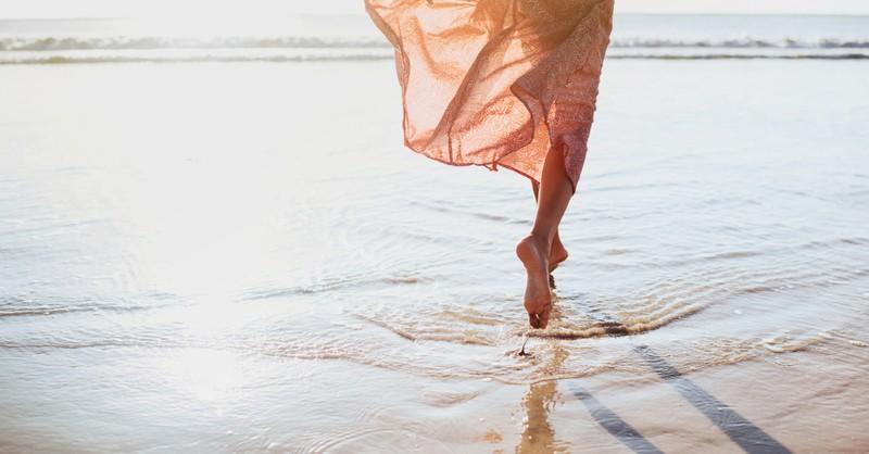 woman running along shore bare feet emotional health