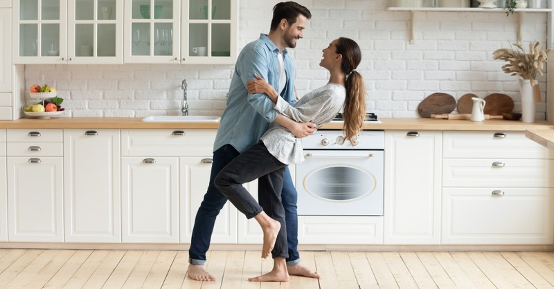 couple dancing to music in the kitchen