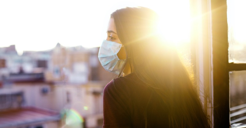 Woman wearing mask looking over balcony at sunset