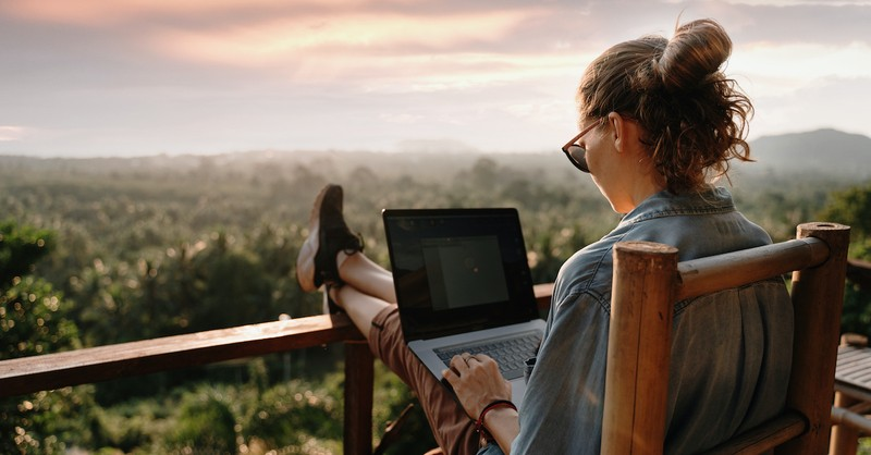 woman working on laptop overlooking a beautiful scenery outside