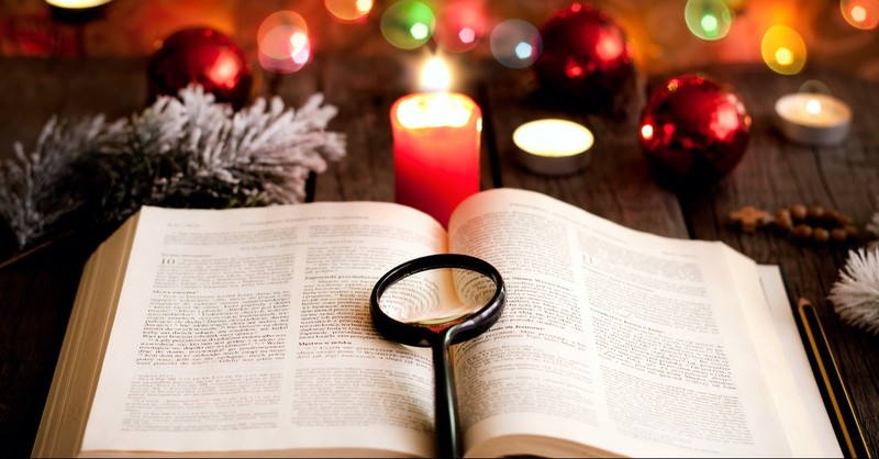 Bible opened in front of a Christmas tree with a magnifying glass on top