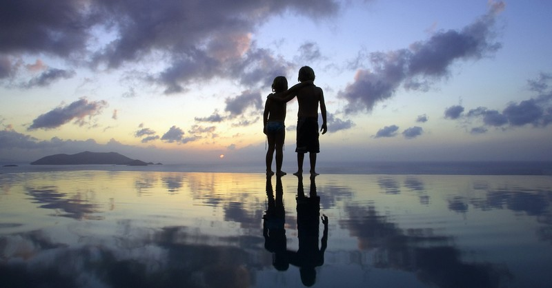 Two children with arms resting on each other's shoulders on the beach at sunset, did Jesus have half-siblings?
