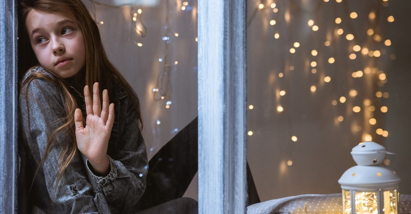 young girl looking sad in window at christmas, when christmas doesn't look very merry