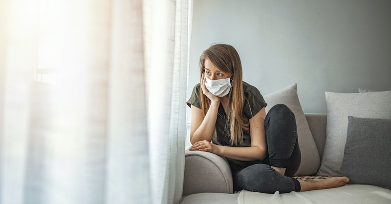 woman wearing mask sitting on sofa looking out window