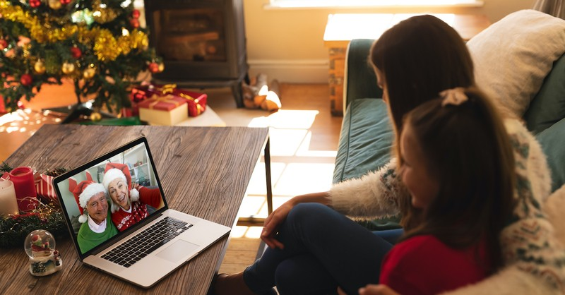 Mom and daughter face-timing grandparents on laptop at Christmas time