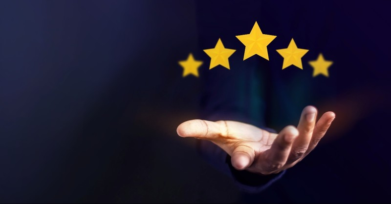 A hand holding out five gold stars