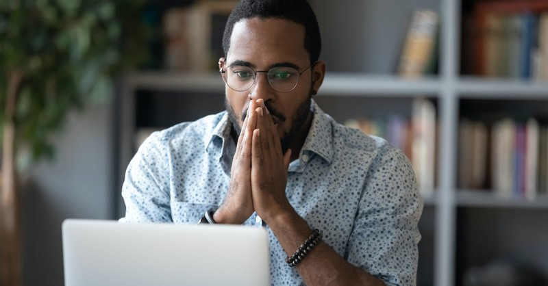 Man staring at computer screen looking stressed, fear of good news