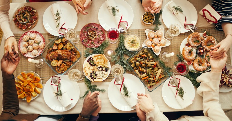 Christmas dinner blessing on decorated table with people holding hands, Christmas dinner prayers