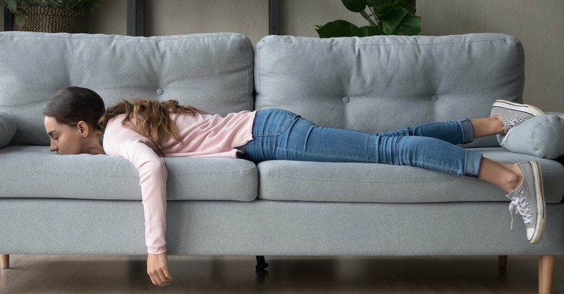 Exhausted woman lying on sofa