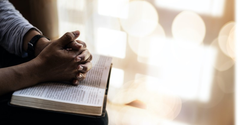 man resting hands on open Bible, Bible verses about trusting God