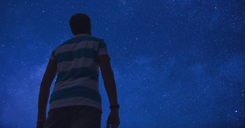 man looking up at starry night sky
