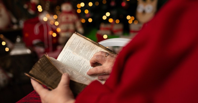 Person reading a Bible near a Christmas tree, things to notice when you read Luke 2