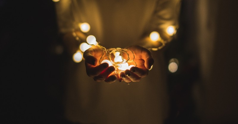 hands holding fairy lights in hands in darkness, top 10 messages of hope in crisis 2020
