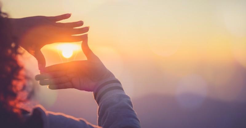 woman holding hands framing sunrise, how to plan spiritual retreat