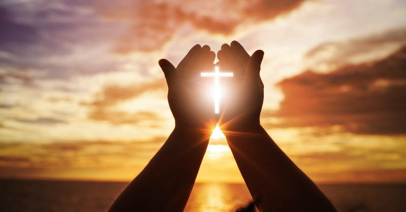 silhouette of prayer hands raised with cross symbol against sunset background, shekinah glory